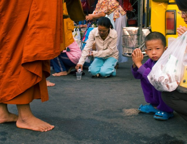 Child giving alms at Chiang Mai Gate Market in Chiang Mai
